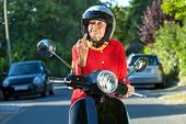 foto of rude  - Senior woman showing the finger while sitting on a scooter bike in a sign of road rage - JPG