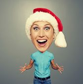 excited and funny girl in red hat over grey background
