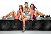 Sexy girls friends sitting on large speaker