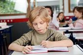 Cute schoolboy writing in book at desk with classmates in background