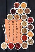 stock photo of qi  - Traditional chinese herbal medicine collection and acupuncture needles with mandarin script calligraphy - JPG