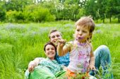 Toddler Eating Flower, Smiling Parents In Back