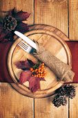Autumn table setting with knife and fork wrapped in rustic burlap