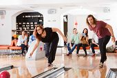 Young man and woman playing in bowling alley with friends in background