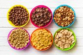 picture of crisps  - top view of various kids cereals in colorful bowls on wooden table - JPG