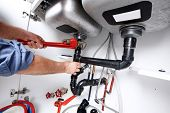 picture of plumber  - Hands of professional Plumber with a wrench - JPG