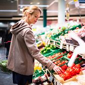 Beautiful young woman shopping for fruits and vegetables in produce department of a grocery store/su