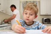 Young Boy Drawing While Father Works In Kitchen