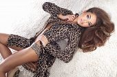 image of nightie  - Sensual fashionable brunette woman lying on the fur posing looking at camera - JPG