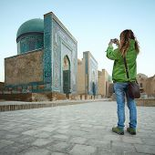 Young lady tourist taking a picture of ancient complex of Shah i Zinda. Focus on buildings. Samarkand, Uzbekistan
