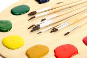 stock photo of bristle brush  - wooden art palette with  paint and brushes - JPG