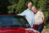 Happy mature couple hugging by their red cabriolet on a sunny day