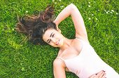 Pretty brunette woman lying on a lawn smiling at camera