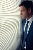 Stern handsome businessman looking out of window in dark room