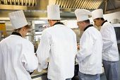 Four chefs working in industrial kitchen while wearing uniforms rear view