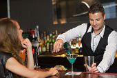 foto of bartender  - Handsome bartender serving cocktail to attractive woman in a classy bar - JPG
