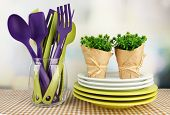 Plastic kitchen utensils in stand with clean dishes on tablecloth on bright background