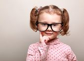 Thinking Kid Girl In Glasses Looking Happy On Copy Space Background