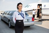 stock photo of jet  - Portrait of attractive airhostess standing against limousine and private jet at airport terminal - JPG
