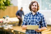 Portrait of mid adult manual worker holding digital tablet with coworker working in background at co