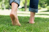 pic of section  - Low section of woman walking on grass in a park - JPG