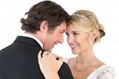 Happy bride and groom embracing while looking at each other over white background