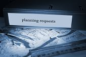 The word planning requests on blue business binder on a desk