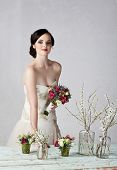 young bride in beige embroidered wedding dress at grunge table with fresh flowers on studio backgrou