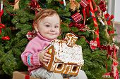 Little girl sits on big cardboard gift box with contented look under Christmas tree, holding gingerbread house in her hands