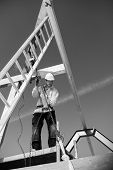 Real construction worker at work with winch on roof construction.Monochrome