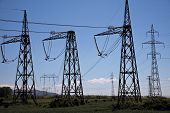 pillars with electricity transmitting lines in field under blue skies