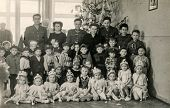 LODZ, POLAND, CIRCA DECEMBER 1970's: Vintage photo of group of children posing with their tutors and parents near Christmas tree
