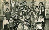 LODZ, POLAND, CIRCA DECEMBER 1970's: Vintage photo of group of little children posing with Santa Cla