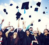 stock photo of white gown  - Graduation Caps Thrown in the Air - JPG