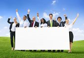 Business People Celebrating with Placard on Hill