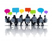 Group of Business People at Meeting Table with Speech Bubbles