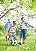African Father and Sons Playing Football/Soccer in a Park