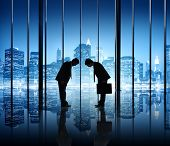 Two Businessmen Bowing in Office with City Lights