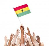 Diverse Multiethnic Hands Holding and Reaching For The Flag of Ghana