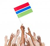 Diverse Multiethnic Hands Holding and Reaching For The Flag of Gambia