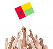 Diverse Multiethnic Hands Holding and Reaching For The Flag of Guinea Bissau