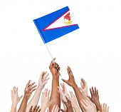 stock photo of samoa  - Diverse Multiethnic Hands Holding and Reaching For The Flag of American Samoa - JPG