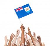 Diverse Multiethnic Hands Holding and Reaching For The Flag of Anguilla