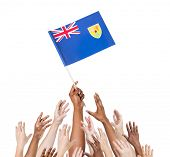 Multiethnic and Diverse Hands Holding The Flag of Turks and Caicos Islands