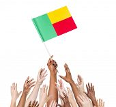 Group Of People Reaching For And Holding The Flag Of Benin