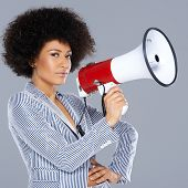 Stylish beautiful young African American woman with curly afro hair and a megaphone with a jaunty attitude standing with her hand on her hip, square format on grey