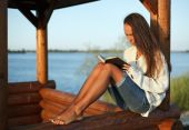 Young Woman Reading Book In Summerhouse On Sunset