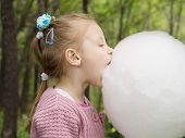 picture of candy cotton  - Young caucasian little girl eating big white cotton candy in the park outdoor - JPG
