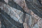 pic of gneiss  - This is a closeup image of a rockface which shows parallel near vertical channels cut into the rock - JPG