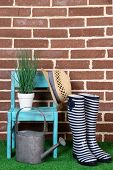 Pair of colorful gumboots, hat, chair and watering can on grass on color wall background